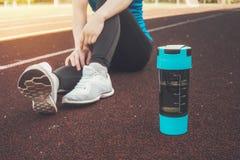 坐下与蛋白质震动或水瓶的女孩在街道在连续锻炼连续锻炼街道以后 库存照片