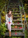 坐下台阶用苹果的女孩 垂直 免版税库存照片