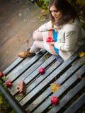 坐下台阶用苹果的女孩 免版税库存图片