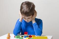 坐下和看对五颜六色的塑料建筑玩具块的被集中的孩子桌 库存图片