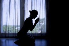坐下在祷告剪影的妇女 免版税图库摄影