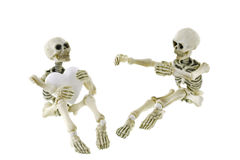 坐与一个一起的骨骼拿着白色心脏 免版税图库摄影