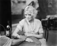 坐与一个人的妇女在看翻倒的餐馆(所有人被描述不更长生存,并且庄园不存在 suppl 免版税库存照片