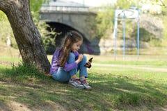 坐与一个手机的草在她的手上和传送信息的逗人喜爱的小女孩在电话机动性 免版税库存图片