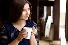 坐与一个杯子热奶咖啡和看窗口的蓝色礼服的女孩 免版税库存照片