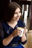 坐与一个杯子的蓝色礼服的女孩热奶咖啡微笑看 图库摄影