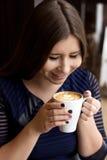 坐与一个杯子的蓝色礼服的女孩热奶咖啡 库存图片