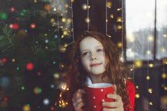 坐与一个杯子的逗人喜爱的小女孩热的可可粉由窗口 库存图片