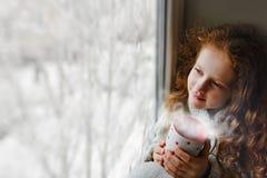 坐与一个杯子的逗人喜爱的小女孩热的coffe由窗口 免版税图库摄影