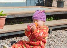 坐与一个瓶的岩石婴儿食品 免版税库存图片