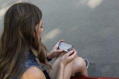 坐与一个电话的女孩在他的手上 库存照片