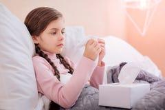 坐与一个箱子的体贴的小女孩餐巾 免版税库存照片