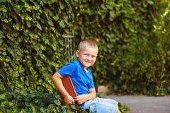 坐与一本书的男孩在围场 库存图片