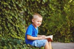 坐与一本书的男孩在围场 图库摄影