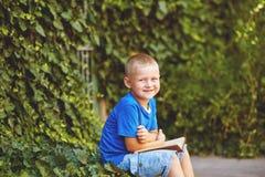 坐与一本书的男孩在围场 免版税库存照片