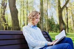 坐与一本书的衬衣的年轻学生女孩在她的手上在绿色公园、科学和教育,读 免版税库存照片