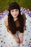 坐与一条开花的裙子的俏丽的深色的妇女 从a的看法 免版税库存图片