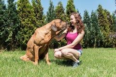 坐与一条狗的女孩在后院 库存图片