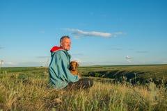 坐与一条狗的愉快的人在大草原 图库摄影