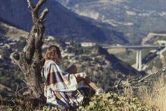 坐与一杯咖啡的一棵树和看农村城市的格子花呢披肩的一个赤裸女孩 格子花呢披肩的一个女孩在别墅对面 免版税库存照片