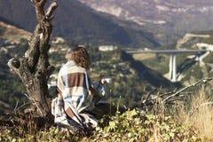坐与一杯咖啡的一棵树和看农村城市的格子花呢披肩的一个赤裸女孩 格子花呢披肩的一个女孩在别墅对面 库存图片