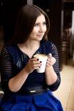 坐与一杯咖啡的女孩 库存照片