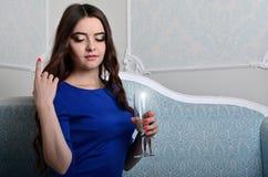 坐与一杯的礼服的女孩香槟 免版税库存照片