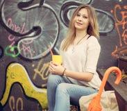 坐与一杯的美丽的年轻白肤金发的妇女午餐的黄色纸袋,与一把多彩多姿的伞在街道画墙壁附近 图库摄影