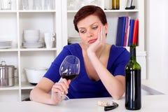 喝一杯红葡萄酒的年轻哀伤的thinkful妇女 免版税库存图片