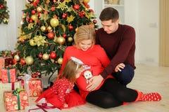 坐与丈夫的欧洲人孕妇拥抱腹部和小女儿在礼物附近在Chistma树下 库存图片