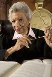 坐与书的资深女性法官 免版税图库摄影