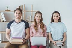 坐与书膝上型计算机的年轻学生 库存照片