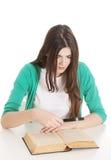 坐与书,读书的年轻美丽的学生,学会。 免版税库存照片