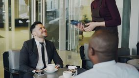 坐与他非裔美国人的同事和付网上帐单的愉快的有胡子的白种人商人使用他的 影视素材