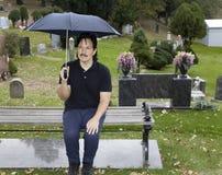 坐与伞的西班牙人在公墓 图库摄影