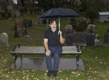 坐与伞的西班牙人在公墓 库存照片