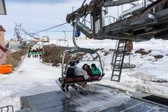 坐与位子的滑雪电缆车和去slo的青年人 免版税库存图片