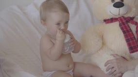 坐与使用与坐在床上的乳瓶,出价的玩具熊是近的她的女婴的逗人喜爱的年轻女人 股票录像