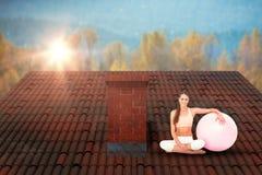 坐与健身球的微笑的适合的少妇的综合图象 免版税图库摄影