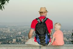 坐与儿子的背包和帽子的年轻人在一个大城市的背景在底部 回到视图 免版税库存照片