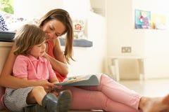 坐与儿子读取故事的母亲户内 免版税库存图片
