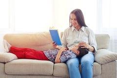 坐与儿子读取故事的母亲户内 库存图片