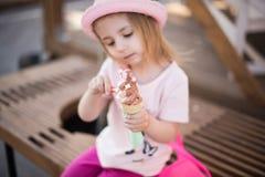 坐与冰淇凌的白肤金发的小女孩 免版税图库摄影