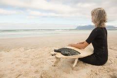坐与冲浪板的保温潜水服的妇女反对多云天空 免版税库存照片