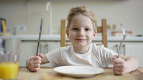 坐与刀子和叉子的高兴的男孩在与碗的午餐期间玉米片和等待的款待 股票录像