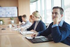 坐与同事的周道的商人工作在办公室 免版税库存照片
