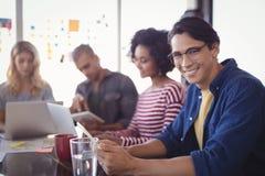 坐与同事的微笑的商人画象在书桌 库存照片