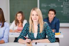 坐与同学的女学生在教室 免版税库存照片