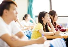 坐与同学的女性大学生 免版税库存照片