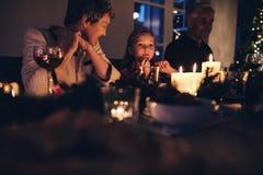 坐与圣诞晚餐的家庭的逗人喜爱的小女孩 图库摄影